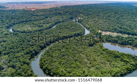 Aerial view of a meandering Amazon tributary river, agricultural land at the horizon Amazonian rainforest, San Jose do Rio Claro, Mato Grosso