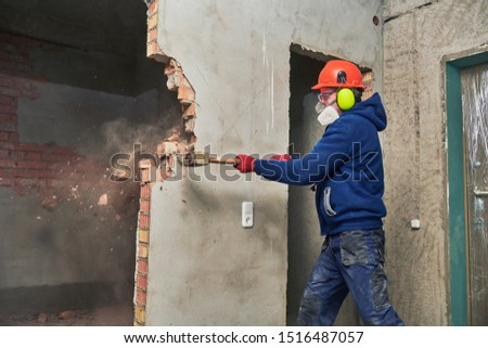 demolition work and rearrangement. worker with sledgehammer destroying wall Royalty-Free Stock Photo #1516487057