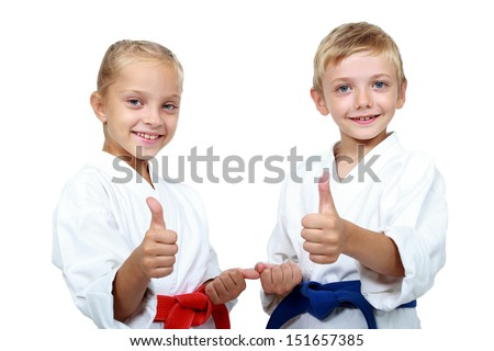 Children athletes with belts show a thumbs up Royalty-Free Stock Photo #151657385