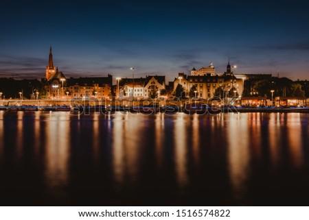 Szczecin. Night view from across the river to the illuminated historic center. Odra river. Chrobry embankments in Szczecin Royalty-Free Stock Photo #1516574822