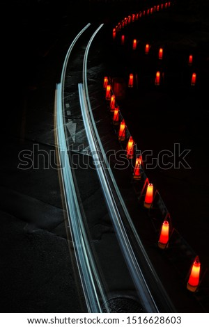 Cool night time long exposure of traffic cones and passing car light trails traveling around a slight curve surrounded by darkness