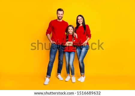 Full length body size photo of family standing confident with daughter arms crossed parents hands in pockets of jeans denim wearing white sneakers red sweaters  isolated over color yellow background #1516689632