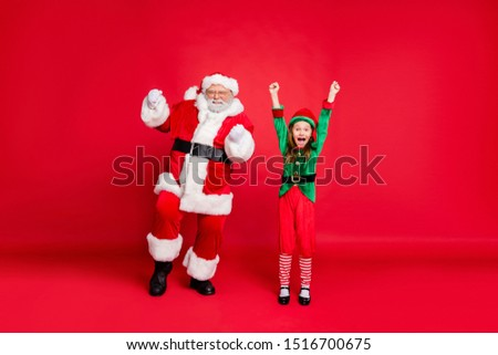 Portrait of cute santa claus elf in green costumes with hat headwear eyewear eyeglasses raising fists screaming yes have newyear party isolated over red background #1516700675