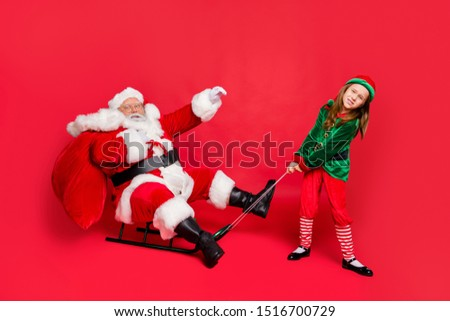 Full size photo of santa claus rider in eyewear eyeglasses spectacles and small redhair elf hat headwear pull sledges carry bag with gift  isolated over red background #1516700729