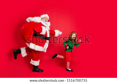 Full body profile side photo of cheerful two fairy runners santa claus elf  in hat headwear carrying heavy bag with presents on midnight wearing eyeglasses eyewear spectacles isolated red background #1516700735