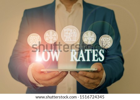 Writing note showing Low Rates. Business photo showcasing A cost of an item or service which is usualy at its smallest price Male wear formal work suit presenting presentation smart device. #1516724345