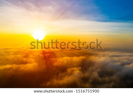 Beautiful golden sunrise sky above fluffy cloudy, dramatic light in twilight sky. Aerial view from drone. #1516751900