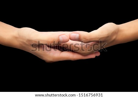 Close up shot of pair of human hands with open hands stacked hands-on each other isolated on a black background and doing famous  Dhyana Mudra or  Gesture Of Meditation. #1516756931