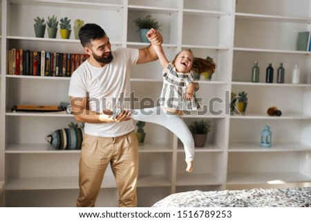 smiling man holding her little sister's arm and leg shaking her, close up photo. #1516789253