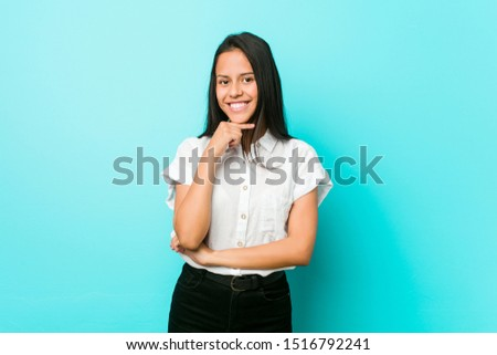 Young hispanic cool woman against a blue wall smiling happy and confident, touching chin with hand. #1516792241