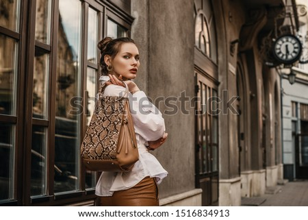 Outdoor fashion portrait of elegant, luxury woman wearing trendy white shirt, holding stylish beige, brown reptile, snakeskin, python print bag, handbag, posing in street. Copy, empty space for text  #1516834913