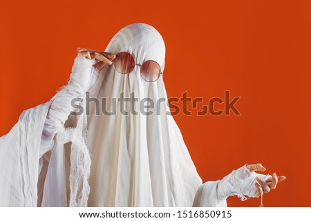Happy Halloween. Cute funny Ghost on a bright orange background. Sheet Ghost costume, Halloween party carnival. Lovely ghost #1516850915