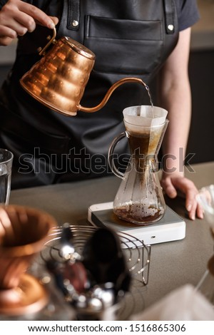 Professional barista preparing coffee using chemex pour over coffee maker and drip kettle. Alternative ways of brewing coffee. Coffee shop concept. #1516865306