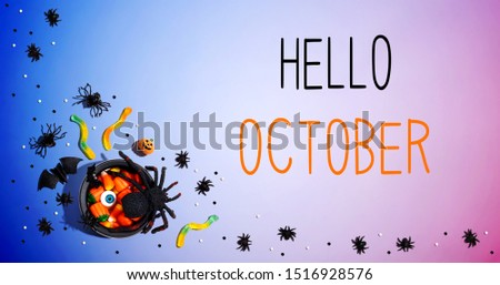 Hello October message with Halloween decorations and witch cauldron