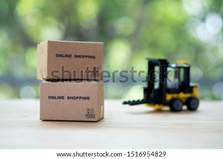 Pile of miniature cardboard boxes on wood table with toy forklift truck background. Concept of retail and concept of online shopping #1516954829