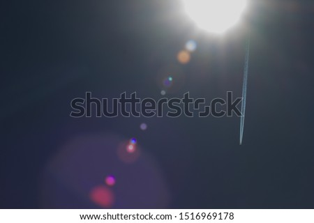 aircraft contrail and  lens flair on summer sky Royalty-Free Stock Photo #1516969178