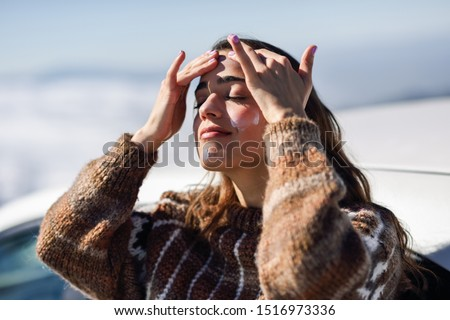 Young woman applying sunscreen on her face in snowy mountains in winter, in Sierra Nevada, Granada, Spain. Female wearing winter clothes. #1516973336