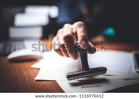 Close-up Of A Person's Hand Stamping With Approved Stamp On Text Approved Document At Desk,  Contract Form Paper #1516976612