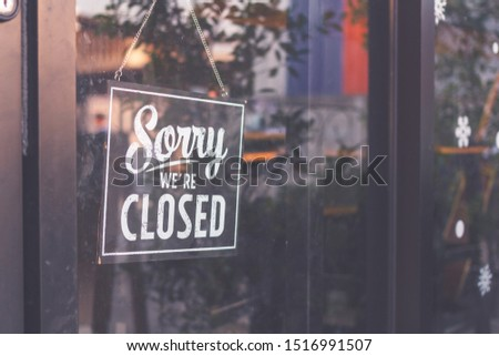 """"""" Sorry we're closed """" sign in black and white, on shop glass door #1516991507"""