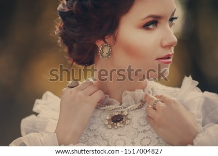 Beautiful girl in a vintage dress, close-up portrait, focus on an old cameo brooch #1517004827