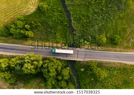 Drone top down view of truck driving remote road over small river during summer day. #1517038325