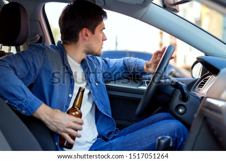Young brunette man is drinking beer behind steering wheel of car. Drunk driver is riding in automobile. Male is violating rules of road. Alcohol driving concept. Deadly danger on route of modern city. #1517051264