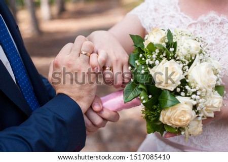 hand of a girl of the bride and hand of a man of the groom, ring, bouquet beautiful #1517085410