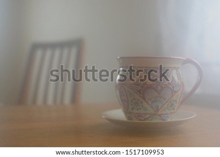 Colorful mug placed on wooden table. Wooden chair in the distance. Misty and unfocused picture reminds good memories, childhood, warmth of countryside home, cozy mornings or holidays. Peaceful picture