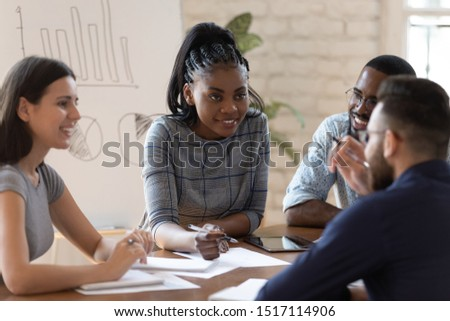 Positive successful mixed race group of managers working together at office, sharing project ideas, writing down notes, preparing financial documentation, developing marketing strategy together. #1517114906