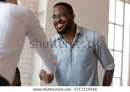 Head shot image joyful african american millennial worker shaking hands with colleague. Confident business partners making agreement before contract signing. Happy teammate thanking for help with job. Royalty-Free Stock Photo #1517119646