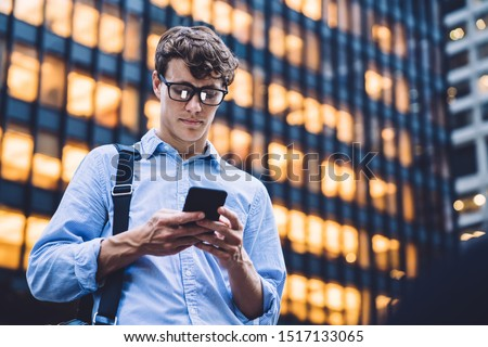 Man in shirt with rolled sleeves and glasses with bag texting on phone standing on background of lighted high building #1517133065