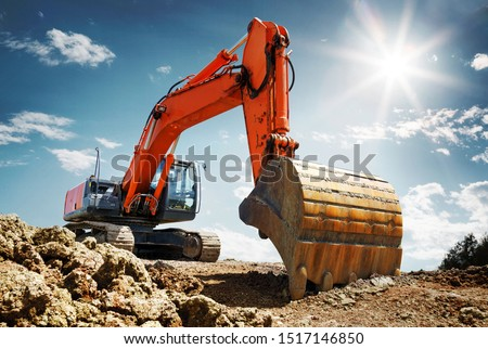 Crawler excavator front view digging on demolition site in backlight #1517146850