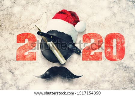 Razor on a plate for foam with a Santa Claus hat on a gray background. Inscription 2020. Greeting card Happy New Year and Merry Christmas for a hairdresser and barber shop. Snow effect