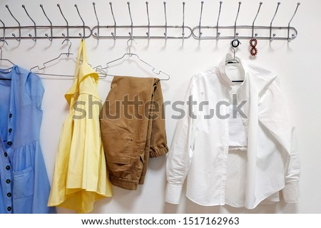Metal hanger on a white wall. On a hanger are four trempels with clothes: a blue sundress, brown trousers, a white shirt, a yellow dress.  Multi-colored women's clothing, summer wardrobe #1517162963