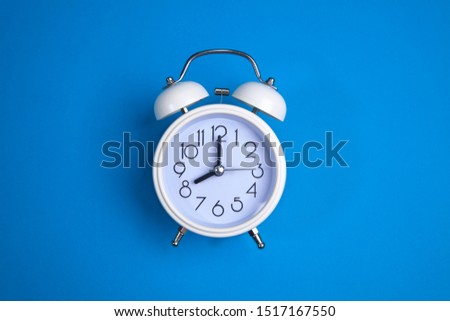 A white alarm clock on a blue background. a top view. a close-up picture representing eight o'clock
