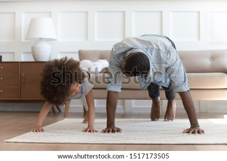 African father and small daughter in casual clothes do pushup pressup exercise on carpet on warm floor in living room, sporty lifestyle, getting physically stronger, have fun, pastime with kid concept #1517173505
