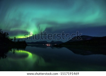 Northern Lights over Abisko National Park in Swedish Lapland. One of the best place to see the Aurora Borealis. Lapporten is also visible in the picture, one of the main symbols of Lapland #1517191469