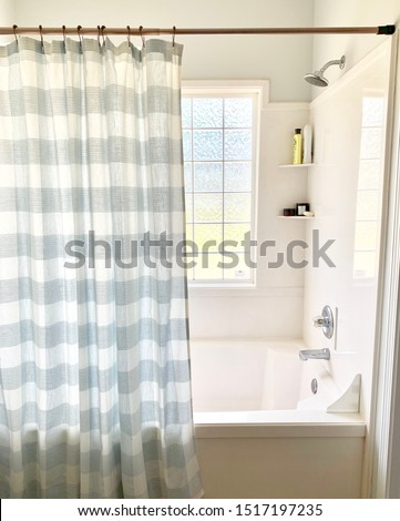 Light blue gingham pattern shower curtain, white marble shower and a large window for natural light. #1517197235