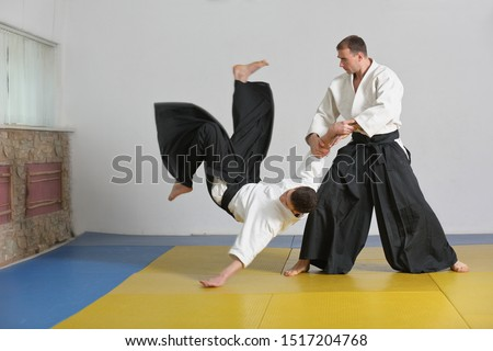 Martial art of Aikido . the athlete demonstrates the technique of Aikido on the tatami in dojo . #1517204768