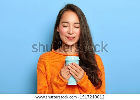 Pleased restful girl with Asian appearance, keeps eyes closed, smiles gently, enjoys drinking aromatic espresso from takeout cup, wears orange jumper, isolated over blue background. People and drink #1517210012