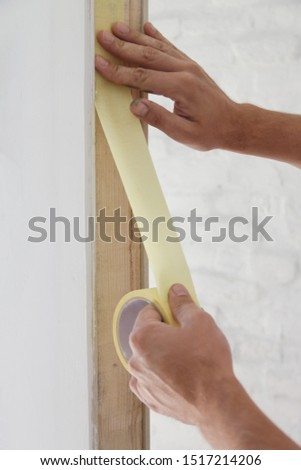 Man putting tape on the wall. The simple step for the quick and easy painting process. Renovation house concept. #1517214206