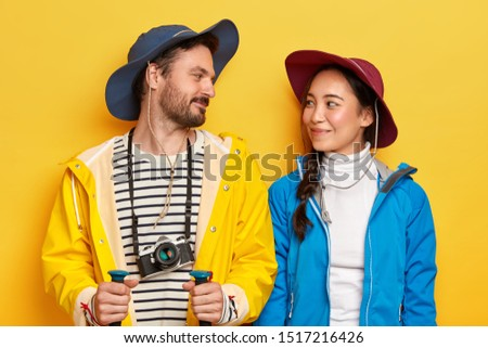 Horizontal shot of active diverse woman and man look gladfully at each other, wear raincoat and jacket, hats, explore new place, trek in mountains hold trekking sticks use retro camera for taking pics