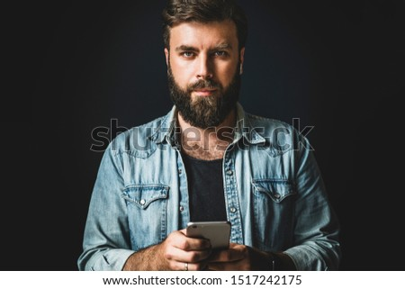 Portrait of young bearded man with smartphone in hand. Hipster guy in denim jacket using mobile phone for online communication in social media, networks. Male person texting messages, checking updates