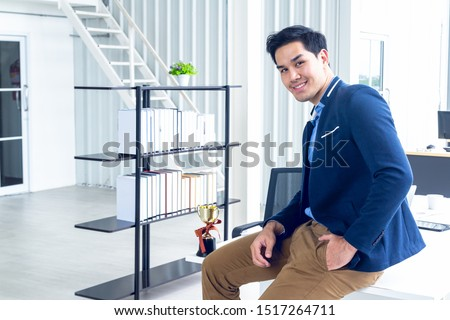 Young businessman sitting in a modern office. He has a feel happy and smile about the result of business profits is positive. On his table have a laptop tablet trophy  and a coffee cup. #1517264711