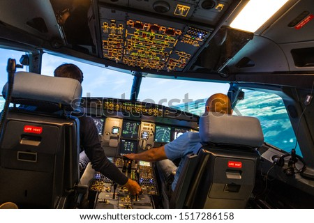 modern airbus airplane cockpit with pilots during a training session in a full flight simulator  Royalty-Free Stock Photo #1517286158