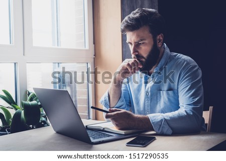 Professional sitting in office in front of laptop. Developer thinking on solutions for work. Home-based student getting distant education. Young serious bearded man in blue shirt working on desktop. #1517290535