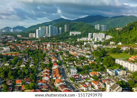 View from above of the subburban area in Penang with a blur view of mountain and buildings from afar #1517293970