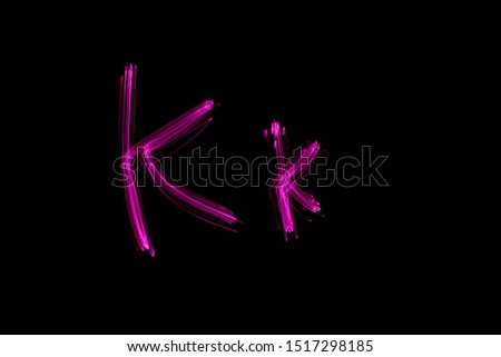 Long exposure photograph of the letter K in uppercase and lowercase in pink neon colour in an abstract swirl, parallel lines pattern against a black background. Light painting photography. #1517298185