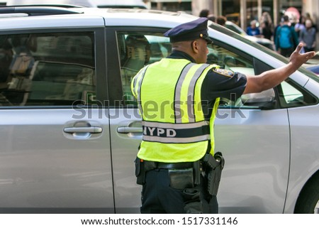 New York City, 9/27/2019: NYPD officer wearing a reflective vest over his uniform is communicating with a motorist while directing traffic Manhattan. #1517331146