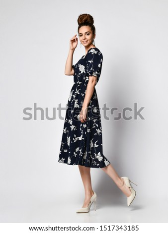Slim curly female model in a silk pale dark dress looking at the camera in full growth. . Cute girl in romantic clothes is going on a date, smiling pretty on a white background. #1517343185